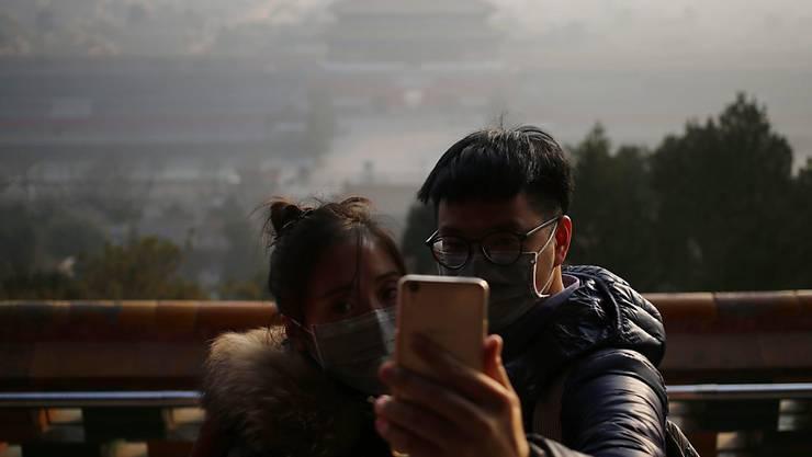 Smog hängt über der Verbotenen Stadt in Peking - und mach Touristen das schiessen von Erinnerungsgfotos schwer.