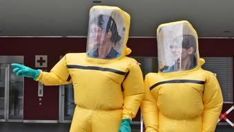 Einweiserinnen in Schutzanzügen nehmen sich als erste der kontaminierten Personen an und leiten sie an die richtige Stelle weiter.