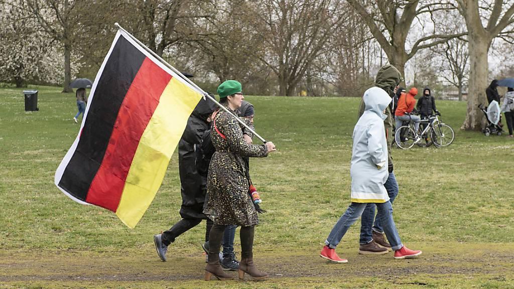 Teilnehmer der Demonstration der Initiative «Querdenken» mit einer Deutschlandfahne. Foto: Boris Roessler/dpa