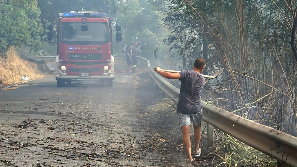 Ein Mann gestikuliert in Richtung Feuerwehr, die mit einem Löschzug eine Straße entlang fährt. Foto: Luigi Salsini/LaPresse via ZUMA Press/dpa