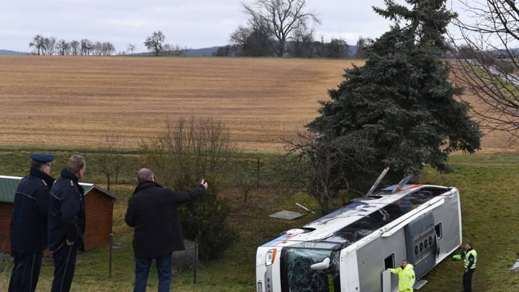 Polizisten stehen beim verunglückten Schulbus. Zwei Kinder verloren bei dem Unfall ihr Leben.
