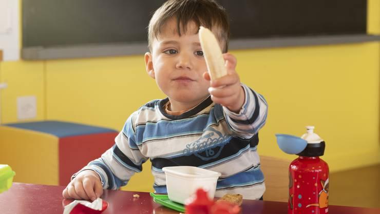 Der Znüni macht besonders Spass: Ein Kind greift während der Essenspause zur Banane .