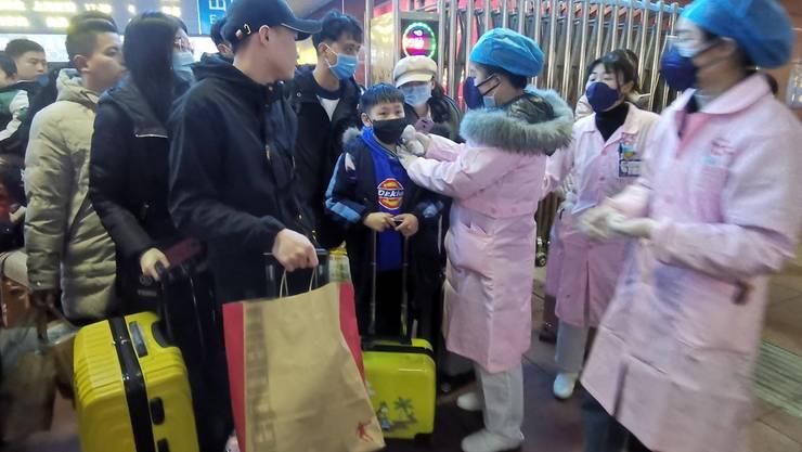 Medizinische Personal misst bei Zugspassagieren in Yingtan City in der Provinz Jiangxi die Temperatur. (Archivbild)