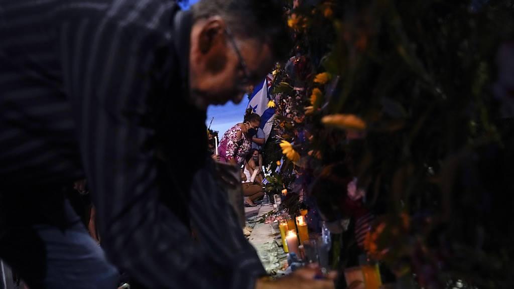 Menschen zünden am 15. Juli Kerzen vor einer Gedenkstätte für die Opfer des Einsturzes des Champlain Towers South Condo Building an. Einen Monat nach dem Teileinsturz hat die Feuerwehr ihre Bergungsarbeiten nun beendet. Foto: Rebecca Blackwell/AP/dpa