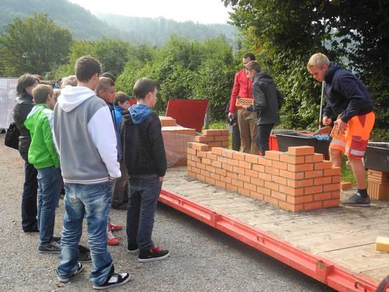Mauerlehrling Till Wälchi zeigt den Schülern wie man mit Ziegel und Spachtel eine Mauer baut