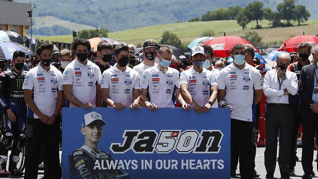 Teammitglieder und Fahrer gedenken dem verstorbenen Jason Dupasquier.