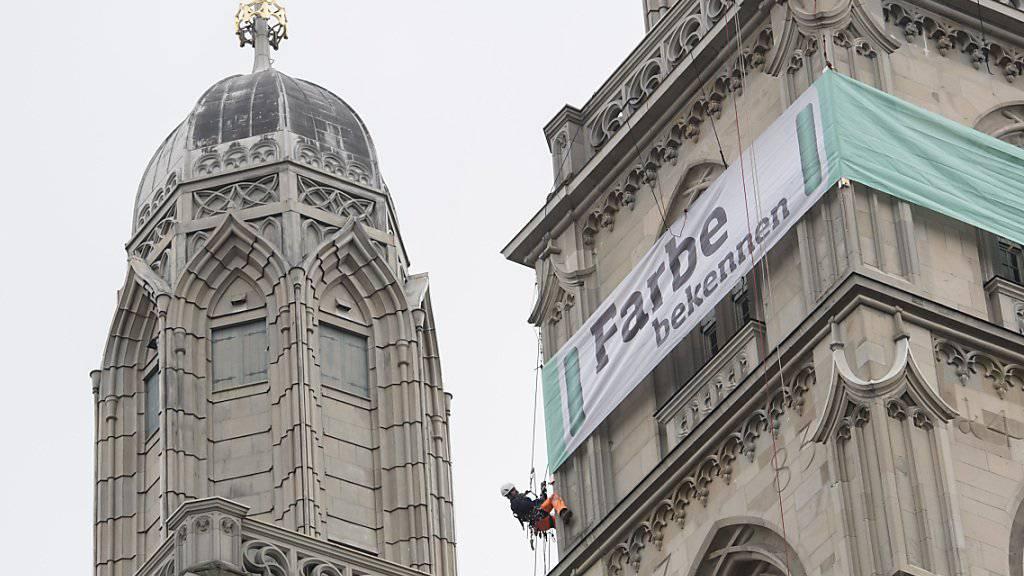 Ein grünes Transparent am Zürcher Grossmünster wirbt seit Montag für die Aktion «Farbe bekennen für eine menschliche Schweiz». Lanciert wurde die Kampagne vom Hilfswerk der Evangelischen Kirchen Schweiz (HEKS)