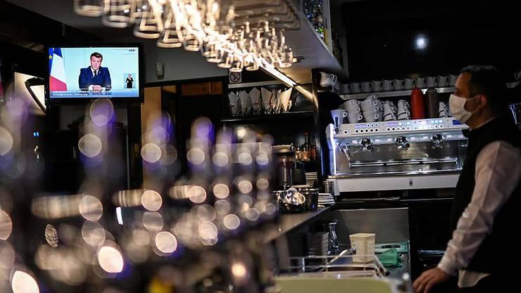 Emmanuel Macron, Präsident von Frankreich, ist auf einem Bildschirm eines Fernsehers in einem Café zu sehen. Foto: Christophe Simon/AFP/dpa
