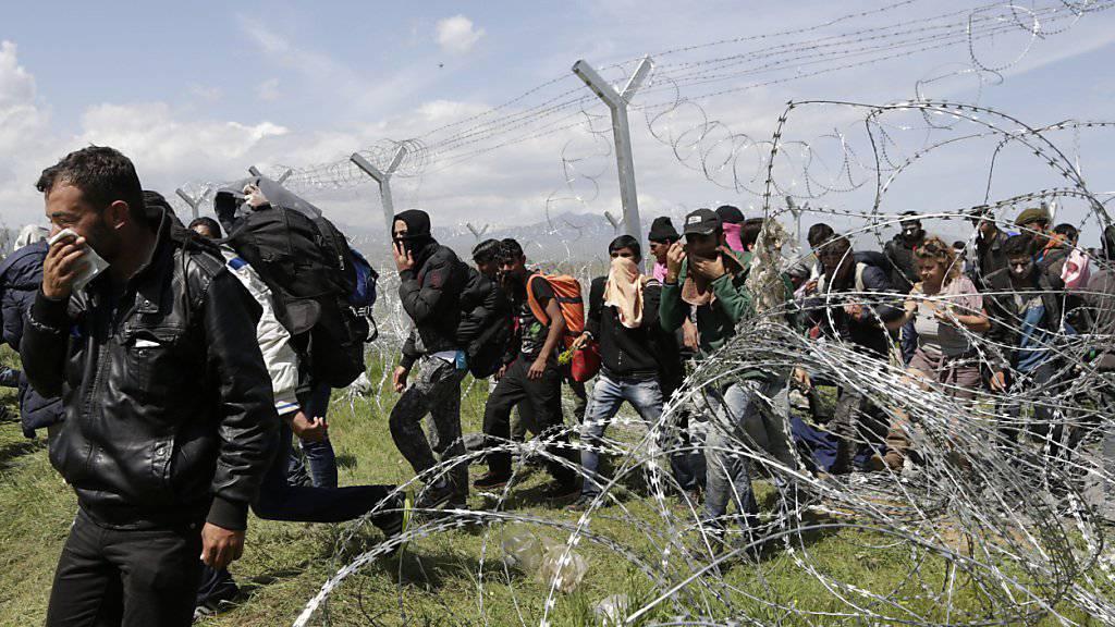Flüchtlingen gelingt es, den Stacheldraht-bewehrten Grenzzaun zu überwinden. Viele von ihnen bedecken ihren Mund wegen des Tränengases.