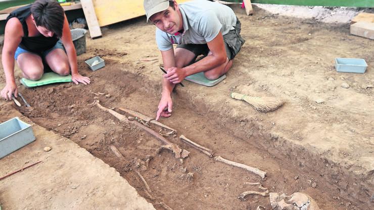 Grabungen im Juli in Unterstammheim:Ein Mann mit einem Schwert – der Archäologe zeigt mit dem Finger drauf – aus dem Frühmittelalter wurde ausgegraben.