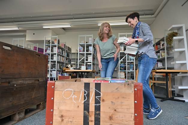 Evi Scherrer und Regula Affolter räumen Bücher aus und verpacken sie in Kisten