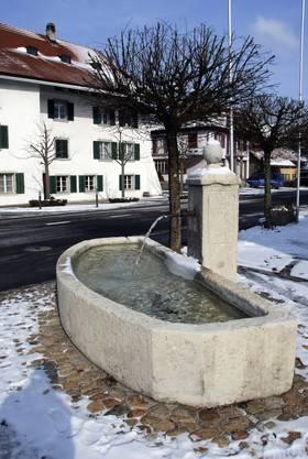 Unterdorfbrunnen mit Blick auf eines der ältesten Häuser im Gäu