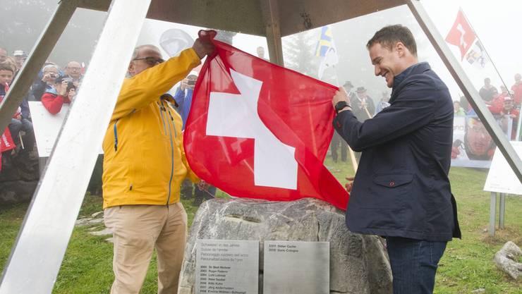 """Die Älggialp gilt als Mittelpunkt der Schweiz. Hier hängt auch die Tafel mit den Namen der """"Schweizer des Jahres"""". Dario Cologna wurde 2013 im Beisein von alt Bundesrat Adolf Ogi darauf verewigt."""
