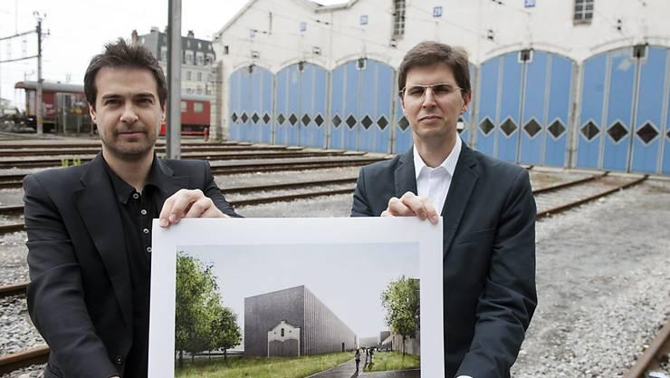 """Die Architekten Alberto Veiga (rechts) und Fabrizio Barozzi zeigen ein Foto ihres Projekts """"Bleu"""" am Ort, wo das neue Kunstmuseum enstehen soll (Archiv)."""