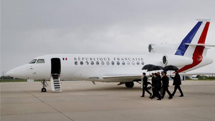 Frankreichs Präsident Macron (l.) marschiert vorneweg zum Regierungsflieger.