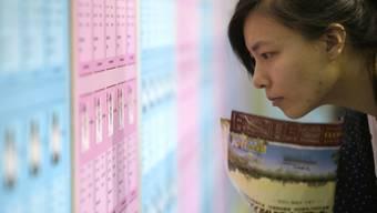 """Eine junge Chinesin blickt auf den Aushang einer Partnerbörse: Der """"Tag der Singles"""" wurde in den Neunziger Jahren von Studenten als Antwort auf den Valentinstag ins Leben gerufen (Archiv)."""
