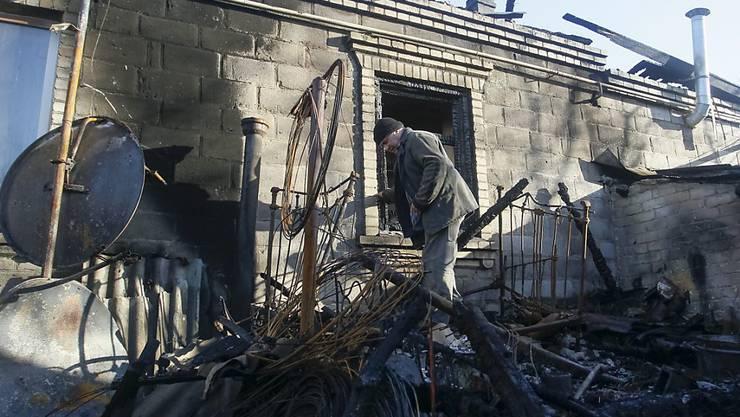 Ein Mann steht in den Trümmern eines Hauses, das bei heftigem Beschuss in der Nähe von Donezk zerstört wurde.