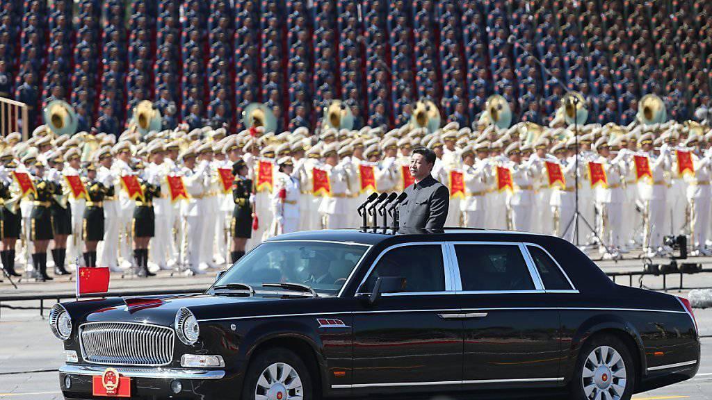 Chinas Präsident Xi Jinping nimmt von einer Limousine aus die Militärparade in Peking ab.