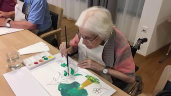 Mit viel Konzentration zum perfekten Bild: eine Seniorin der Malgruppe an der Vollendung ihres Gemäldes.
