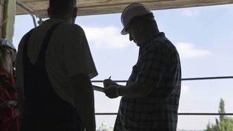 Bauarbeiter werden auf einer Baustelle kontrolliert (Archiv)