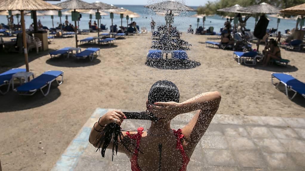 Eine Frau duscht an einem Strand des Dorfes Lagonissi, einige Kilometer südwestlich von Athen. Eine der schwersten Hitzewellen seit den 1980er Jahren ist über Südosteuropa hereingebrochen. In Teilen Griechenlands steigen die Temperaturen auf über 40 Grad Celsius. Foto: Yorgos Karahalis/AP/dpa