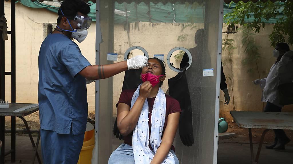 Ein Mitarbeiter des Gesundheitswesens entnimmt einer Frau einen Nasenabstrich. Foto: Mahesh Kumar A/AP/dpa