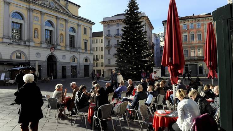 Passanten geniessen bei frühsommerlichen Temperaturen auf der Piazza della Riforma in Lugano die Sonnenstrahlen