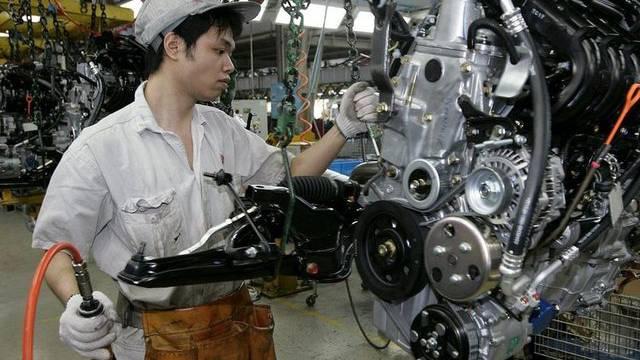 Ein Arbeiter baut in einer chinesischen Honda-Produktionsstätte an einem Auto-Motor (Archiv)