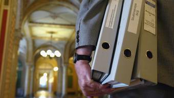 Ein mit Akten beladener Bundesbeamter unterwegs im Bundeshaus. (Symbolbild)