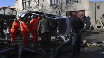 Afghanische Sicherheitskräfte und Gemeindearbeiter entfernen ein beschädigtes Fahrzeug nach einem Bombenanschlag. Bei einem erneuten Anschlag in der afghanischen Hauptstadt Kabul sind mindestens fünf Menschen getötet worden, vier von ihnen Ärzte. Foto: Rahmat Gul/AP/dpa