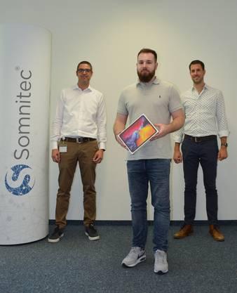 Vanja Rohr (links), CEO der Hauptsponsorin Somnitec AG, und Philipp Heri, Gemeindepräsident von Gerlafingen, übergeben dem Gewinner Pascal Steiner (Mitte) das iPad Pro.
