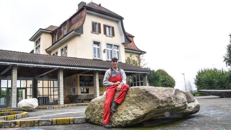 Pius Wietlisbach auf einem der Findlinge auf dem Schulhausplatz, die er platziert hat.
