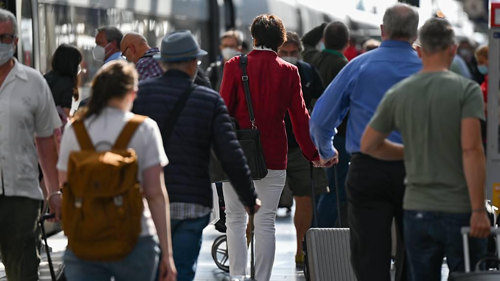 ARCHIV - Bahnreisende gehen auf einem Gleis im Frankfurter Hauptbahnhof an einem ICE der Bahn vorbei. Foto: Arne Dedert/dpa