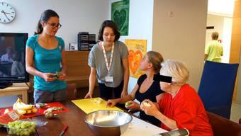 Drei Jugendliche vom Jugendrotkreuz bereiten mit einer Seniorin aus dem Alterszentrum Fruchtsalat zu.