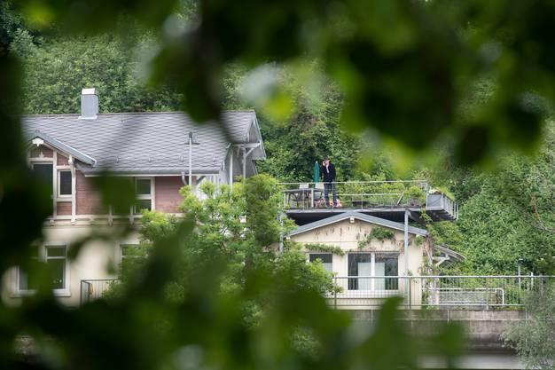 Der Schweizer Schriftsteller Christian Haller (rechts auf der Terrasse) gibt vom deutschen Laufenburg aus ein Interview. Reportage von der Grenze zwischen der Schweiz und Deutschland während der Coronakrise, 13. Mai 2020.