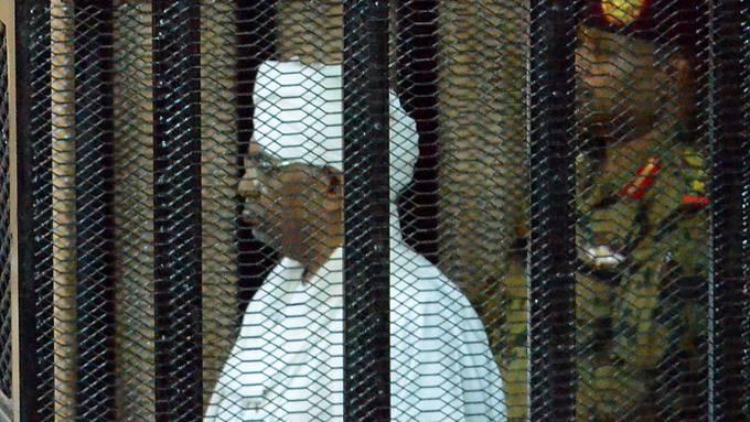 Der in eine weisse sudanesische Robe gekleidete angeklagte frühere Machthaber Sudans, Omar al-Baschir, verfolgt den Prozess aus einem Gitterkäfig im Gerichtssaal.