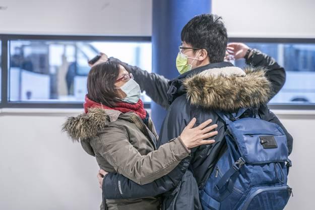 Zwei chinesische Touristen in Rovaniemi, Finnland, tragen Masken.