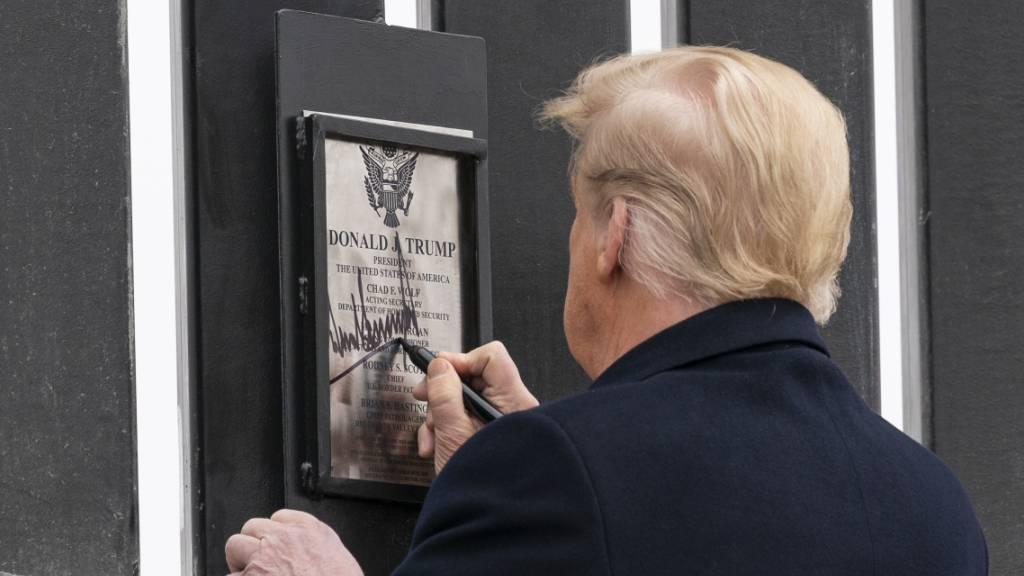 Donald Trump unterzeichnet eine Plakette an einem Abschnitt der US-Mexiko-Grenzmauer. Foto: Alex Brandon/AP/dpa