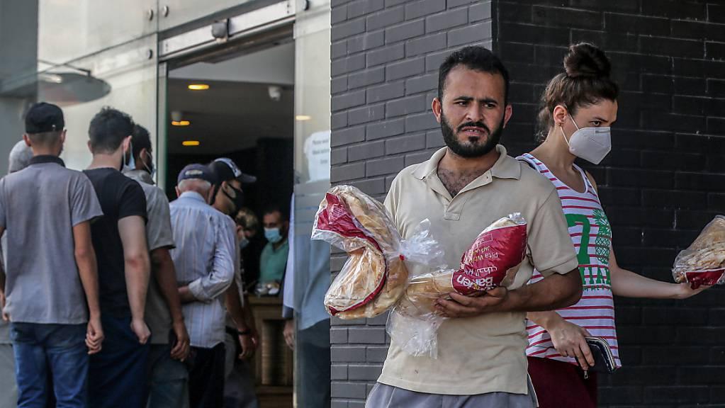 Menschen verlassen eine örtliche Bäckerei, nachdem sie inmitten der schweren Treibstoffknappheit und der Stromausfälle, die das Land inmitten einer der schlimmsten Wirtschaftskrisen der letzten Zeit lähmen, eine Packung Brot geholt haben. Foto: Marwan Naamani/dpa