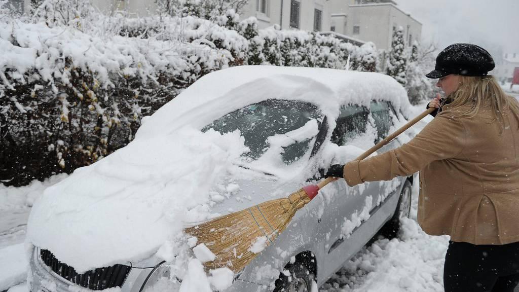 Da hilft nur noch der Griff zum Besen: Das Auto vom Schnee zu befreien ist oftmals ein Kraftakt.