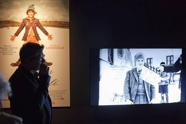 Ein Besucher steht vor dem Schellen-Ursli Filmplakat und verfolgt einen Beitrag zu den Dreharbeiten am Filmset von Xavier Koller, in der Ausstellung von Alois Carigiet im Landesmuseum Zue