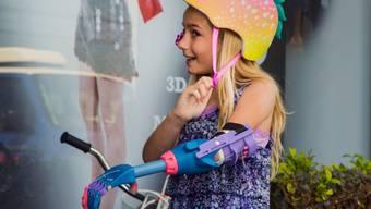 Dank einer Handprothese aus dem 3D-Drucker kann Faith Lennox, 7, wieder Velofahren. Dem Mädchen aus Kalifornien musste wegen eines Geburtsfehlers der Arm amputiert werden.