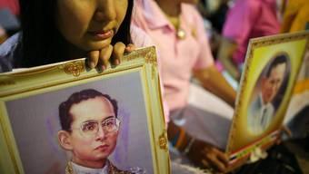 Hunderte Thailänderinnen und Thailänder harren vor dem Spital aus, in dem der schwerkranke König behandelt wird. und beten.