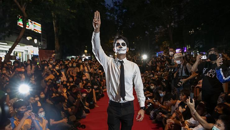 Ein pro-demokratischer Demonstrant hält bei einer Protestaktion, die wie eine Modenschau aussieht, seine Finger zum symbolischen Drei-Finger-Gruß des Widerstands in die Höhe. Die Demonstrierenden fordern weiterhin den Rücktritt von Ministerpräsident Prayut, eine Neuwahl und umfassende Reformen. Foto: Gemunu Amarasinghe/AP/dpa