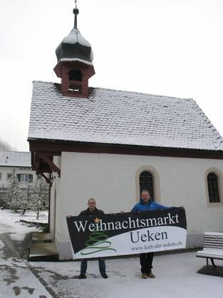 Christian Bader und Gregor Rippstein vom Organisationskomitee präsentieren die Blache mit dem Signet des Ueker Weihnachtsmarktes vor der Kapelle in Unterueken wo der Weihnachtsmarkt stattfinden wird.