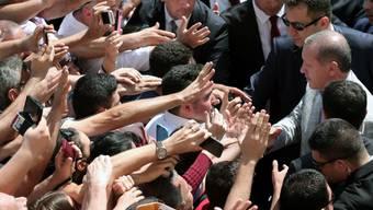 Erdogan schüttelt Hände von Anhängern bei der Stimmabgabe