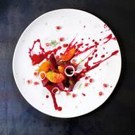 Rande des Wahnsinns von Claudio Del Principe2 Randen Salz 1 Moro- oder Tarocco-Orange, Saft Gutes Öl (z. B. kalt gepresstes Sonnenblumenöl)Roter Kampot-Pfeffer aus der Mühle Balsamicoessig und Sonnenblumenöl zum Marinieren 1 Tropea-Zwiebel 1 EL Condimento bianco (weisser Balsamicoessig) oder Weissweinessig 1 Blutorange Ein wenig Fenchelkraut zum GarnierenNach Belieben 2 EL GranatapfelkerneZubereitungDie Randen ungeschält in leicht salzigem Wasser weich kochen, dann schälen. Eine Rande im Mixer pürieren und durch ein feines Sieb passieren. Den Orangensaft zugeben und bei mittlerer Hitze sirupartig einkochen. Ab und zu mit etwas Wasser strecken, wenn sich der Sirup am Topfboden festsetzt. Etwas auskühlen lassen und dann ein gutes Öl mit dem Schneebesen einrühren, bis die Flüssigkeit homogen ist und schön glänzt.Die andere Rande in Spalten schneiden und mit Salz, Pfeffer, Balsamico und Sonnenblumenöl 30 Minuten marinieren. Die Tropea-Zwiebel in Ringe schneiden, kurz mit dem Condimento bianco und 1 Esslöffel Wasser aufkochen, in eine Schüssel umgiessen, 10 Minuten ziehen lassen.Die Blutorange filetieren, das Fenchelkraut zupfen. Die Sauce mit einem Esslöffel aus dem Handgelenk schwungvoll auf den Teller kleckern. Die Randenspalten und Orangenfilets darauf verteilen, mit rotem Kampot-Pfeffer, nach Belieben Fenchelkraut, Zwiebelringen und Granatapfelkernen garnieren.Rezept aus: «all'orto» Claudio Del PrincipeAT-Verlag, 256 SeitenFr. 39.90.