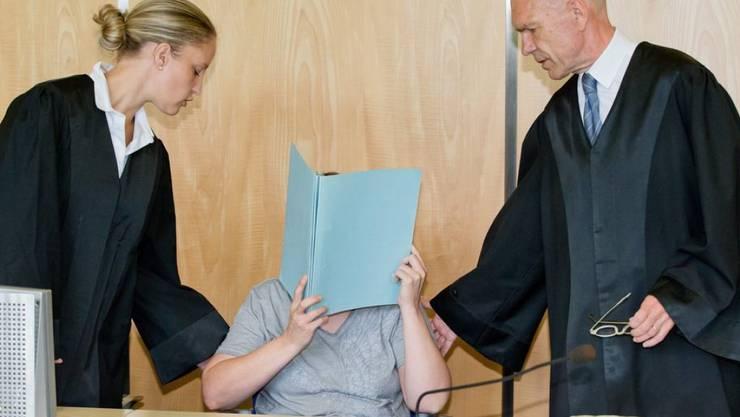 Die Mutter von acht toten Babys in Bayern muss für 14 Jahre hinter Gitter. Das Bild zeigt die 45-Jährige, die vor Gericht ihr Gesicht mit einem Aktenordner verdeckt, zusammen mit ihren Anwälten.