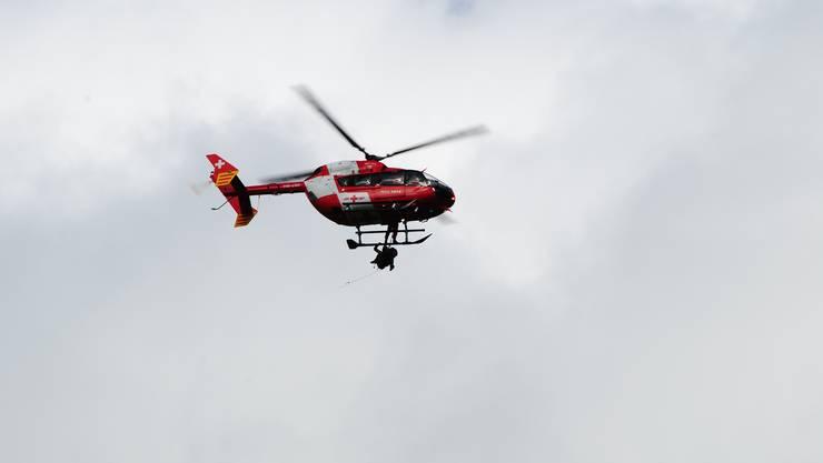 Ein Helikopter der Rega beim Einsatz am Balmfluhköpfli. Die verletzte Person wird unterhalb des Helis transportiert.