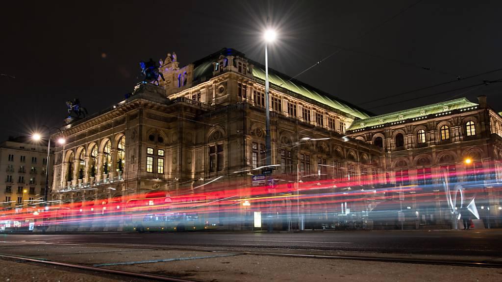 ARCHIV - Die Lichter vorbeifahrender Autos sind vor der Wiener Staatsoper am Abend zu sehen (Langzeitbelichtung). Die Wiener Staatsoper wird am 7. September mit der Premiere von «Madama Butterfly» ihren seit sechs Monaten wegen der Corona-Krise unterbrochenen Spielbetrieb wieder aufnehmen. Foto: Robert Michael/dpa-Zentralbild/dpa